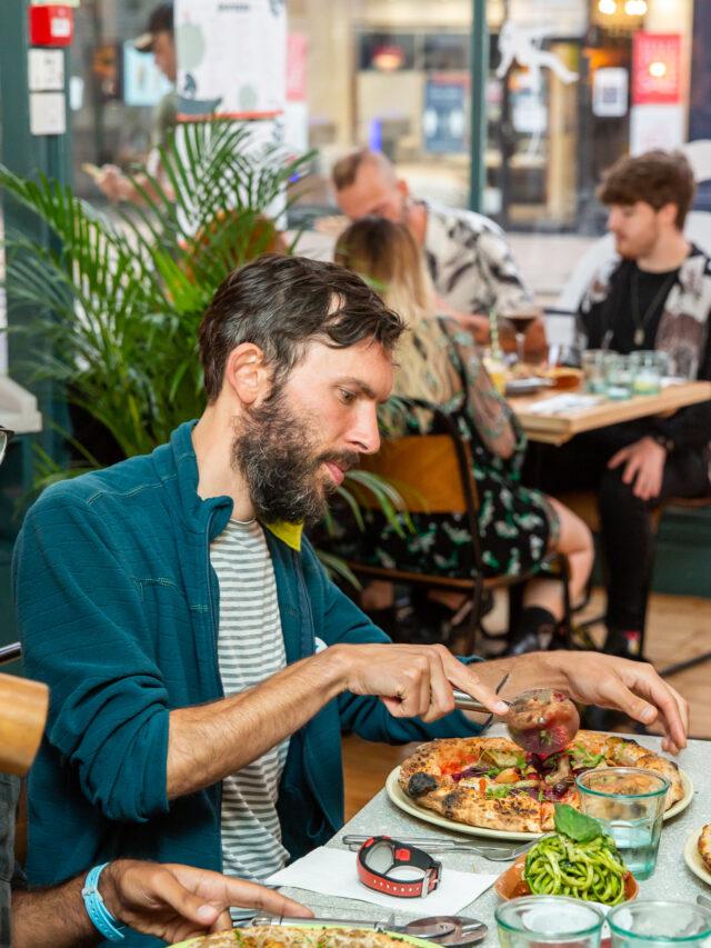 A man cutting a pizza in Purezza Hove