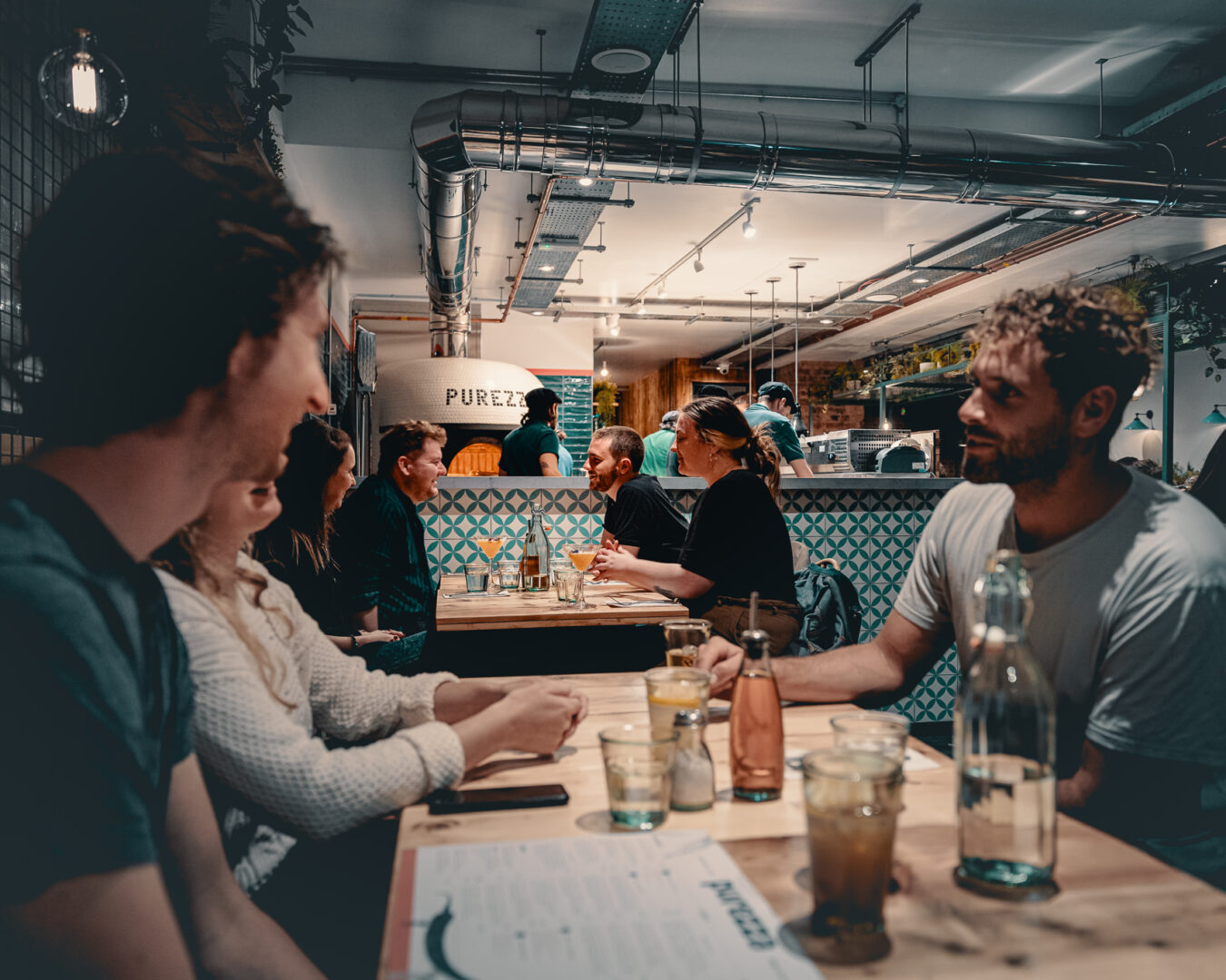 A group of people dining at Purezza Bristol during a busy evening.