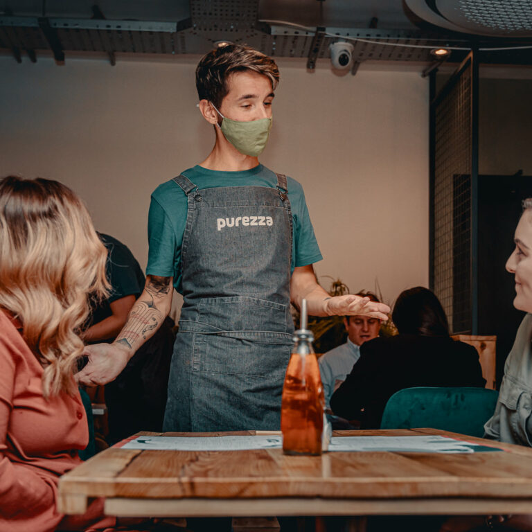 A waiter serving two people at Purezza Manchester