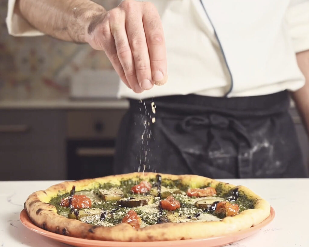 chef sprinking nutritional yeast onto a gluten free pizza